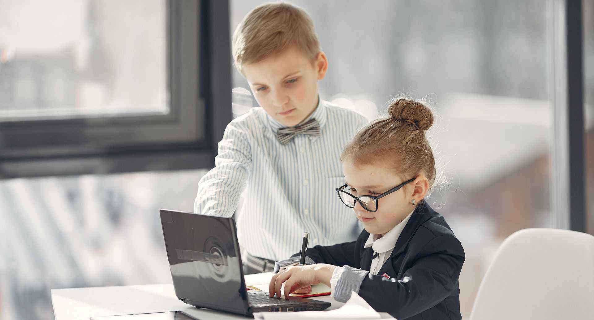 Two children dressed like executives working at a desk